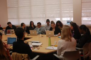 A group of UCLA Graduate Students are seated around a conference table, participating in a seminar with Dr. Sara Ahmed