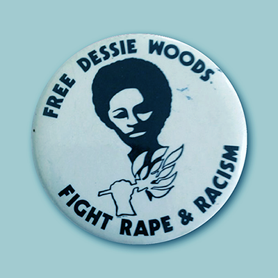 "A metal button that says ""FREE DESSIE WOODS"" and ""FIGHT RAPE & RACISM"" with a drawing of a Black woman in the center."