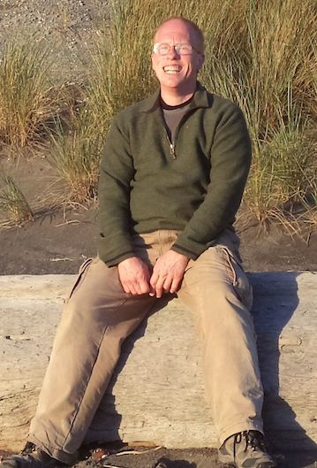 Photo description: Eli sits on driftwood log, smiling in the sun.