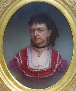 A framed painting of philosopher Sarah Dorsey. Dorsey has dark, curled hair and wears a red, ruffled dress.